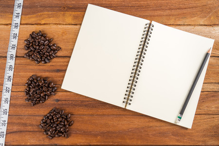 Wooden Clipboard attach planning paper with pencil on top beside coffee bean tape measure photo