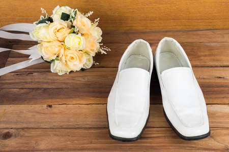 Wedding bouquet with groom's shoes on wood floor background