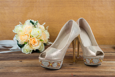 Wedding bouquet with bride's shoes on wood floor background