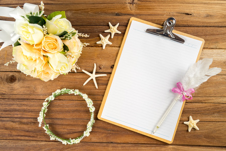 Wooden Clipboard attach planning paper with pen on top beside rose headband tiara bouquet starfish