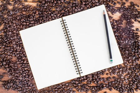 Pencil notebook and coffee beans on wooden background