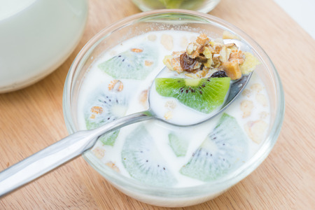 Breakfast, eating cereal, pick up spoon, scoop cereal with fresh kiwis and milk, ready to eat Banco de Imagens