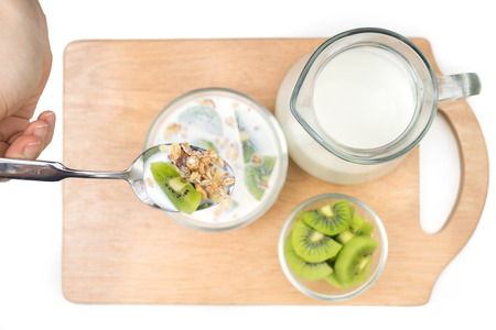 Breakfast, eating cereal, pick up spoon, scoop cereal with fresh kiwis and milk, ready to eat, top shot