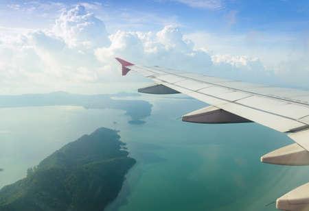 caba�a: avi�n volando sobre el oc�ano y la isla Foto de archivo