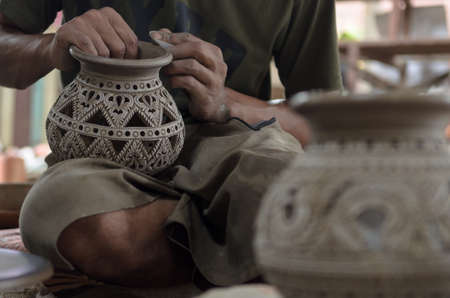 human hand working a pottery vase