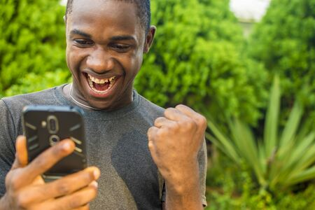 excited and happy young african man viewing something on his phone celebrating Imagens