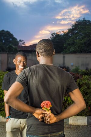 young black man holding flowers behind his back waiting to surprise his lover