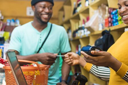 Junger afrikanischer Mann, der in einem Einzelhandelsgeschäft mit seiner Kreditkarte an einem Point-of-Sale-Terminal bezahlt?