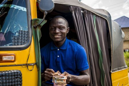 young african man driving a rickshaw taxi counting his money smiling