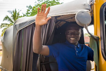 young african man driving a tuk tuk taxi smiling on a very sunny day waving to a passenger Stock Photo