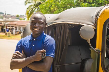 young african man standing near an auto rickshaw smiling with arms crossed holding keys