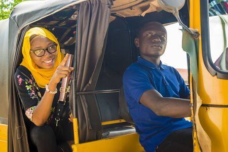african man driving a auto rickshaw taxi being annoyed by a female passenger who's talking to him Stock Photo