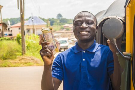 cheerful african man winner holding some money celebrating and jubilant standing next to an auto rickshaw taxi outdoor Stock Photo