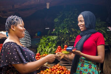 close up of an african woman selling food stuff in a local african market holding a mobile point of sale device collecting a credit card from a customer Stock Photo