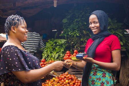 primo piano di una donna africana che vende prodotti alimentari in un mercato africano locale in possesso di un dispositivo mobile per punti vendita che raccoglie una carta di credito da un cliente