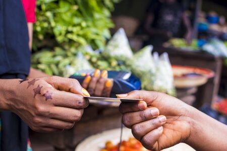 close up of an african woman selling in a local african market holding a mobile point of sale device collecting a credit card from a customer Stock Photo