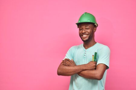 handsome excited young black man wearing a hard hat and holding a screwdriver feeling excited giving thumbs up gesture