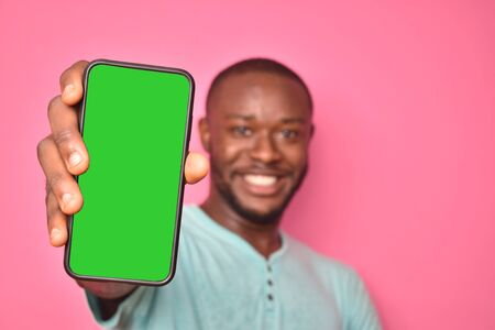 handsome excited young black man feeling excited while showing his phone screen
