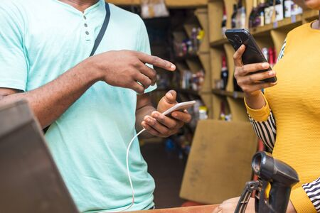 a young black man paying in a supermarket by doing a transfer with his mobile phone