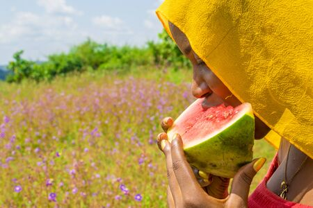 pretty young african woman eating watermelon outside