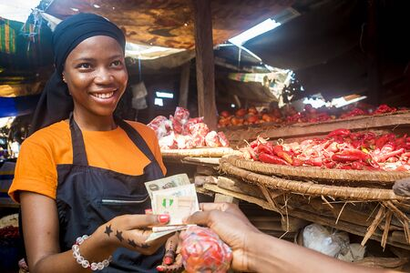 young african woman selling tomatoes in a local african market collecting money from a paying customer Stock Photo