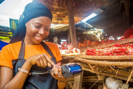 young african woman selling tomatoes in a local african market using her mobile pos device