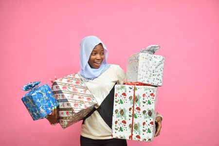 beautiful young black lady holding lots of gift boxes and presents looking surprised Фото со стока