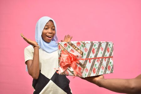 pretty young black woman feeling excited and surprised while receiving a gift from someone