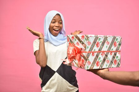 pretty young black woman feeling excited while getting a gift from someone