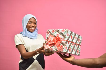 pretty young black woman smiling while receiving a gift from someone