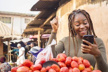 excited young african woman in a local african market viewing her phone celebrating