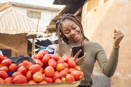 excited young african woman in a local african market viewing content on her phone celebrating