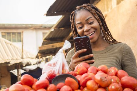 beautiful young african woman in a local african market using her smartphone