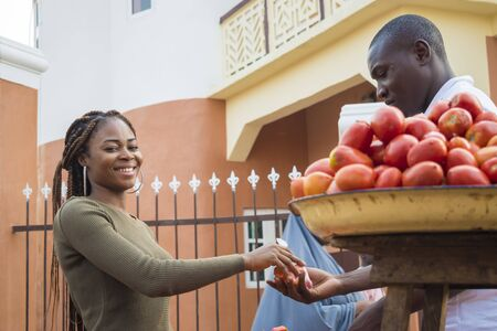 beautiful young african woman selling tomatoes in a local african market to a customer Standard-Bild