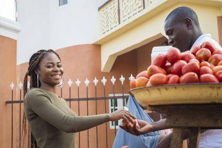 schöne junge afrikanische frau, die tomaten auf einem lokalen afrikanischen markt an einen kunden verkauft Standard-Bild