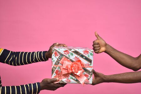 someone giving a gift box to another person, black people, hands only, doing a thumbs up