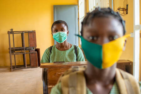 african primary school pupil's sitting in class, wearing face masks, and observing physical distancing