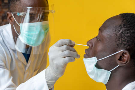 black medical personnel taking nasal sample for covid-19 testing