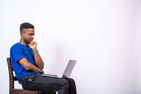 african man looking puzzled while using his laptop Stock Photo