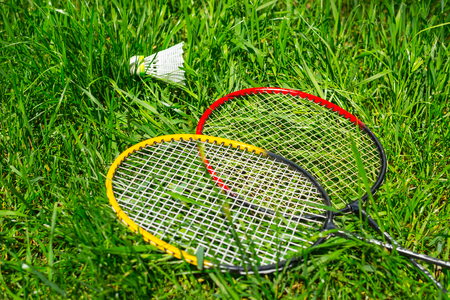 Rackets for badminton with an white shuttlecockon fresh grass with copy space Фото со стока
