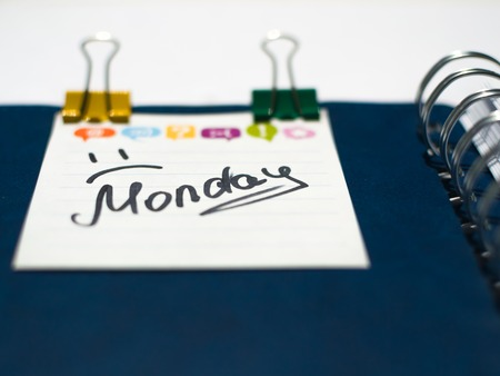the name of the day of the week written on a sticky sheet in a blue notebook with metal springs