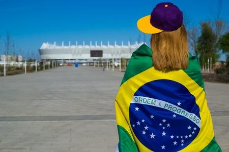 girl cheerleader heading to the football stadium with Brazil flag in yellow purple cap