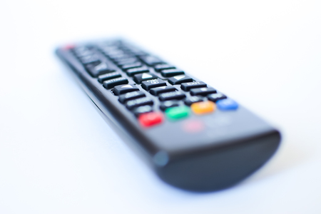 especially heavily blurred black remote controls for the TV on a white background, closeup