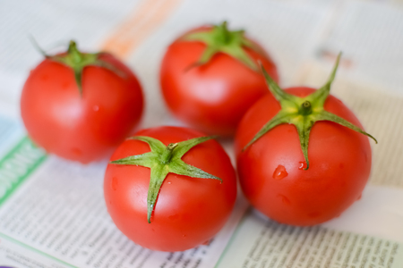 red ripe juicy tomatoes with green ponytail in rustic style on newspaper, background blurred Stock Photo