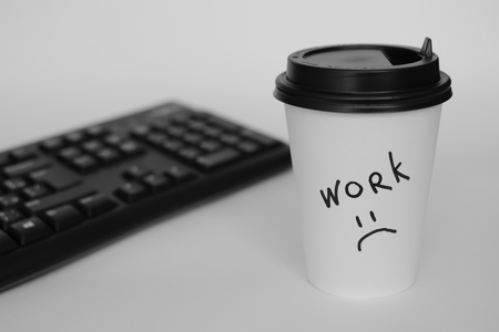 black keyboard and a Cup of coffee. the inscription on the paper Cup.