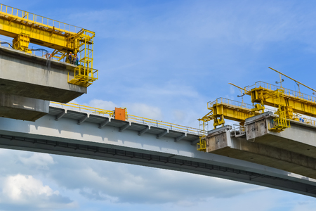 the unfinished part of the road bridge over the river. reconstruction of part of the span, work at height. Stock Photo