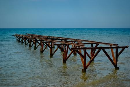 Hierro sin usar, puente oxidado por la tarde en la diagonal se incluye en el mar turquesa. Foto de archivo