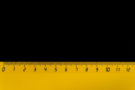 yellow ruler on a black background 12 centimeters. 免版税图像