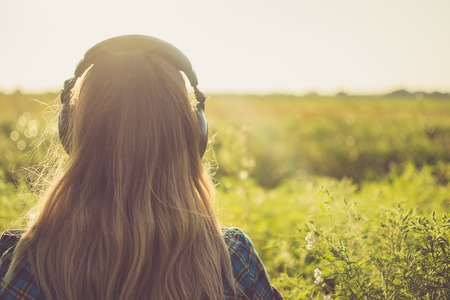 girl with headphones back view. looks into the distance with nature in the horizon. 版權商用圖片