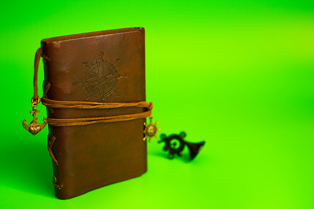 vintage brown leather note pad. green background 免版税图像